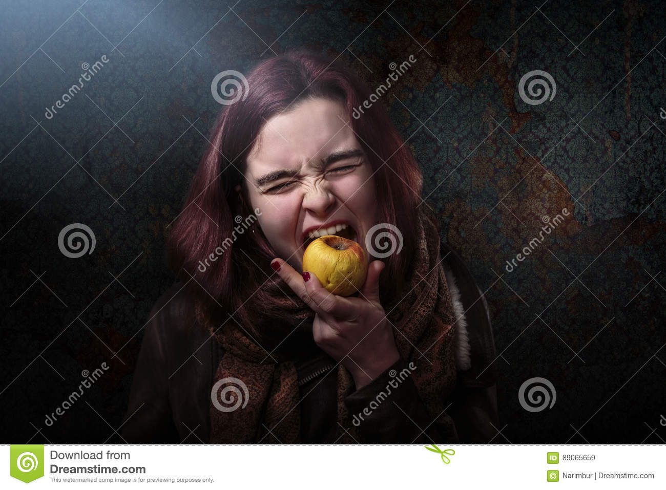 Woman is biting in an old apple