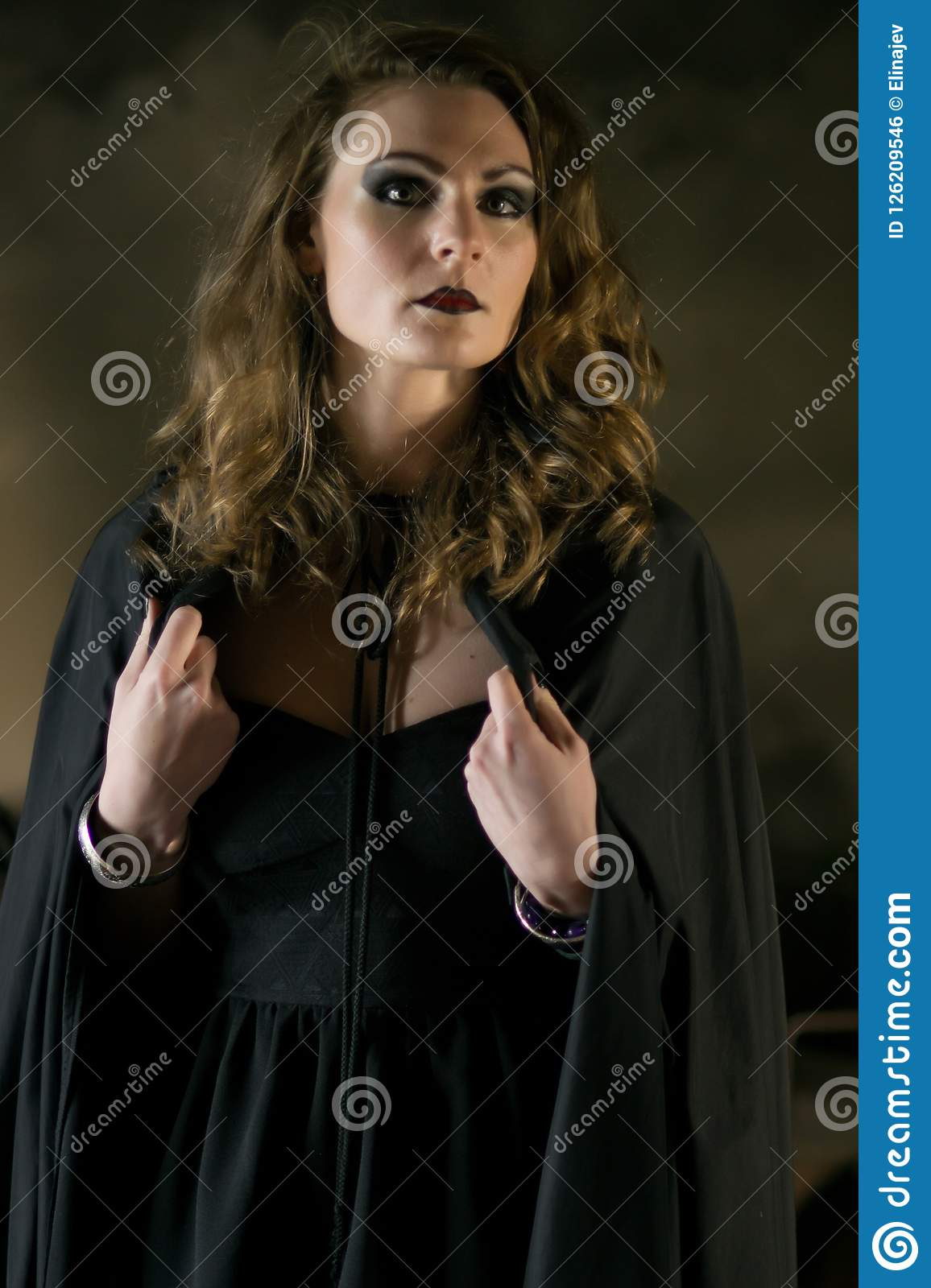 Beautiful witch in black mantle on Halloween