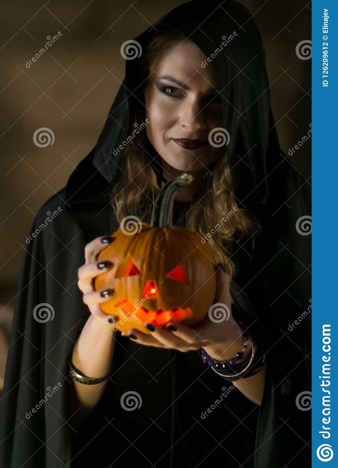 Beautiful witch in black mantle with a pumpkin face on Halloween