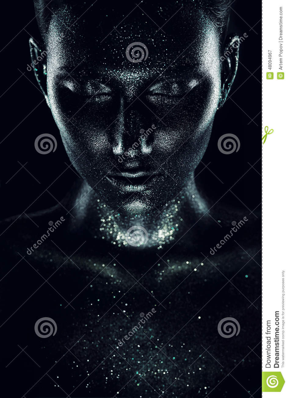 Woman in black paint with sparkles in dark