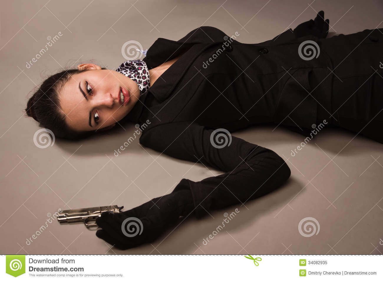 Woman In A Black Suit With Gun Lying On The Floor Royalty