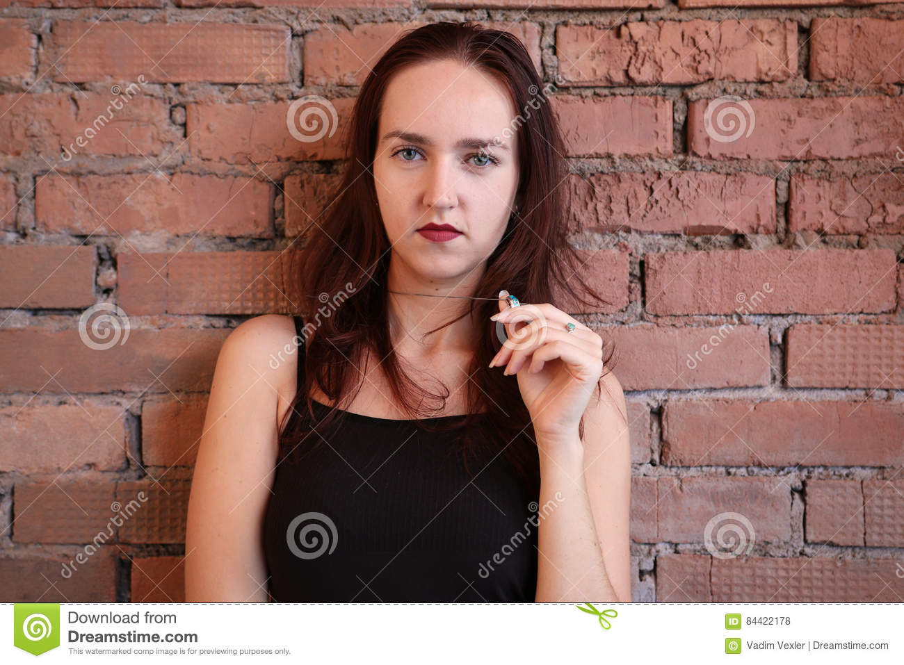 The Woman In Black Top Poses Near A Brick Wall