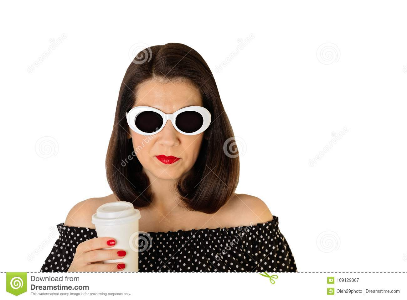 Woman in a black and white dress with polka dots and white sunglasses holding a glass of coffee.