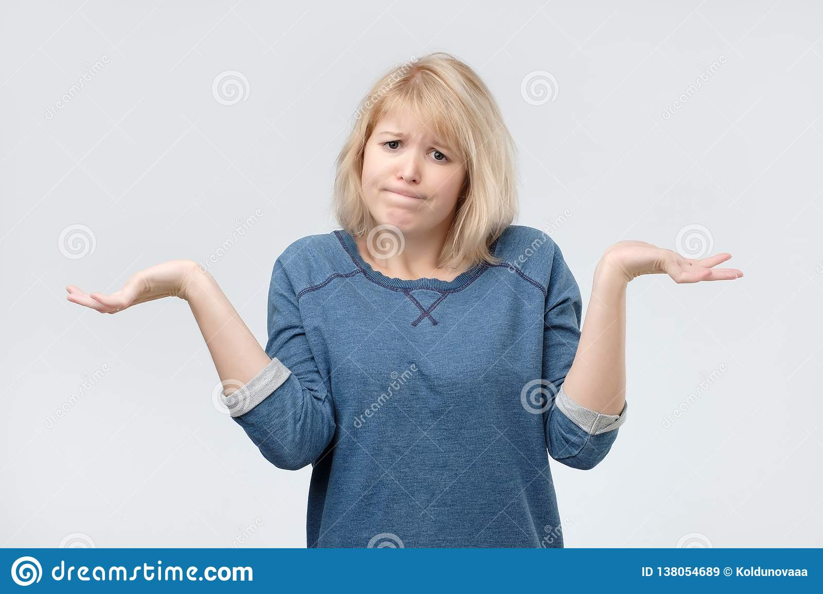 Woman with blonde hair looking in confusion, shrugs shoulders as do not know answer, being clueless