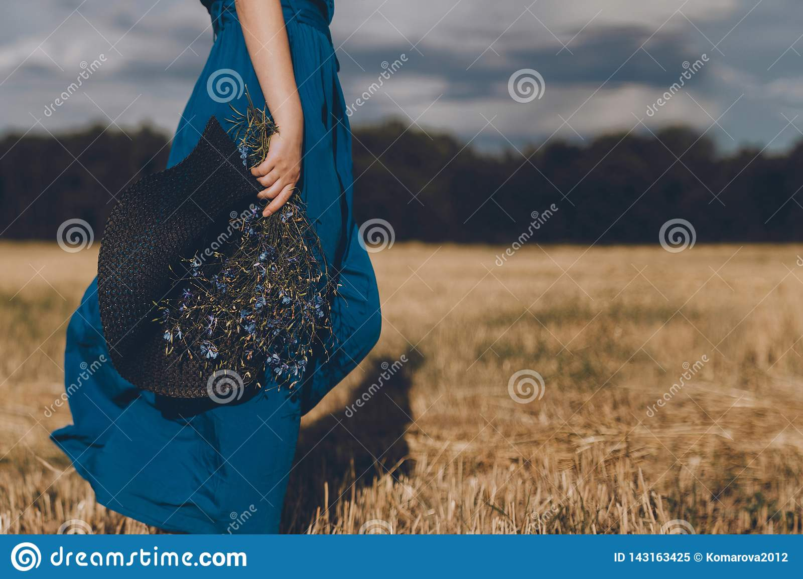 Woman in blue dress with a hat in her hand and bouquet walks around the yellow field
