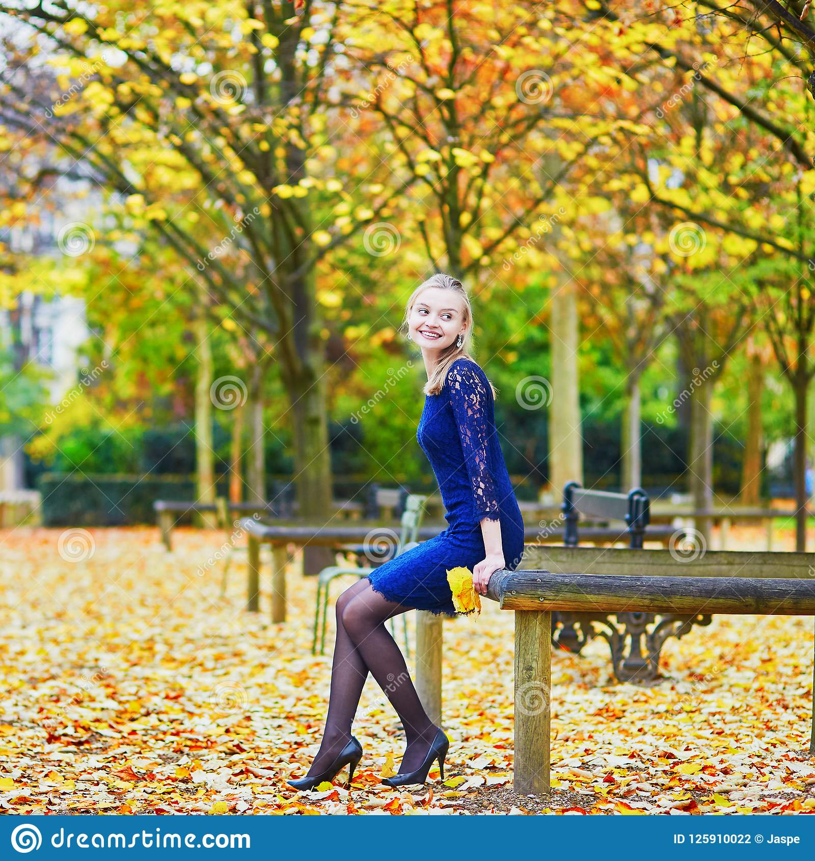 Woman in blue dress in the Luxembourg garden of Paris on a fall day