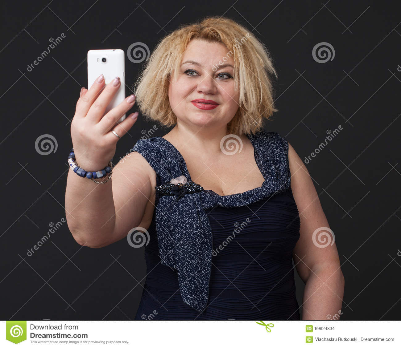Close up mature blonde woman in a blue dress is making selfie, gray  background