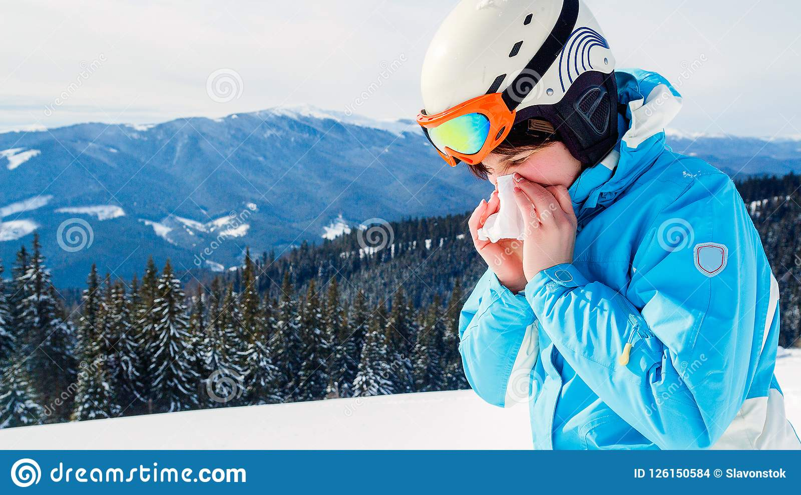 A woman in a blue ski suit is holding a handkerchief and wiping her nose. Skier with cold