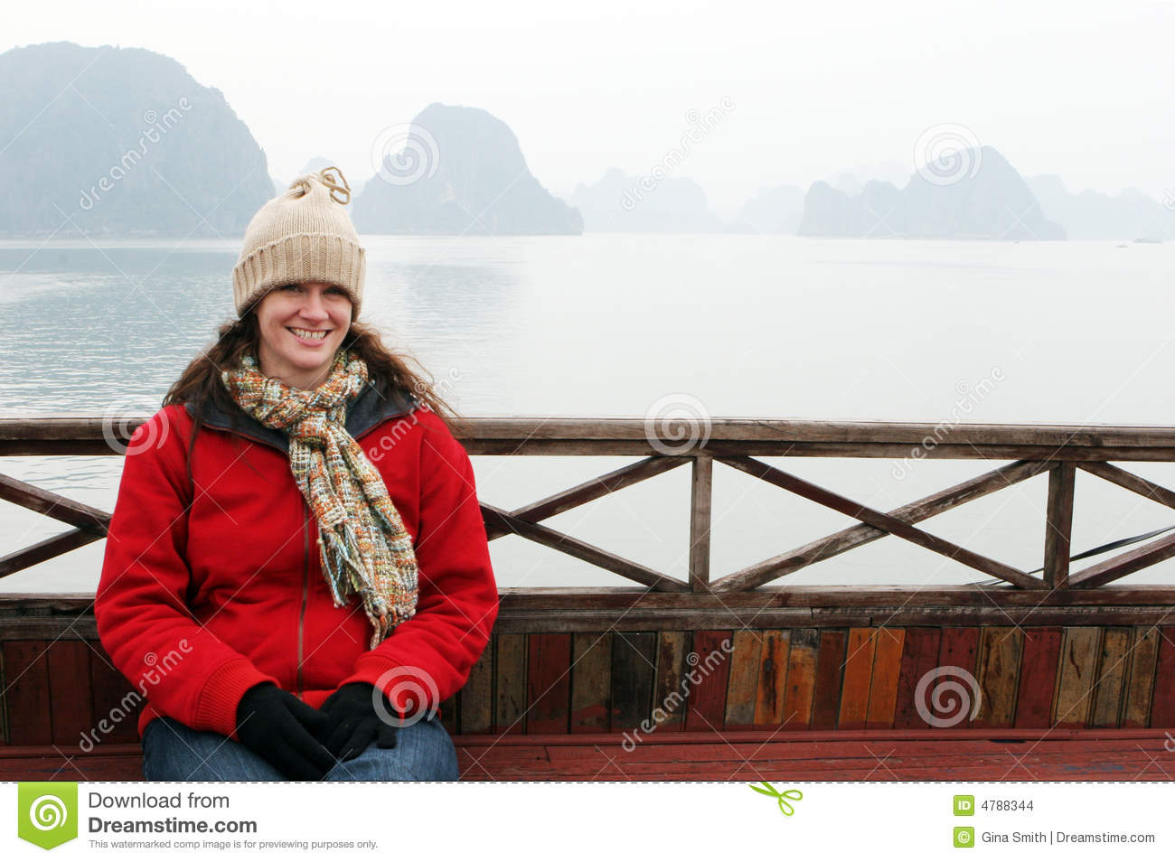 Woman on the deck of a boat dressed in winter clothing.