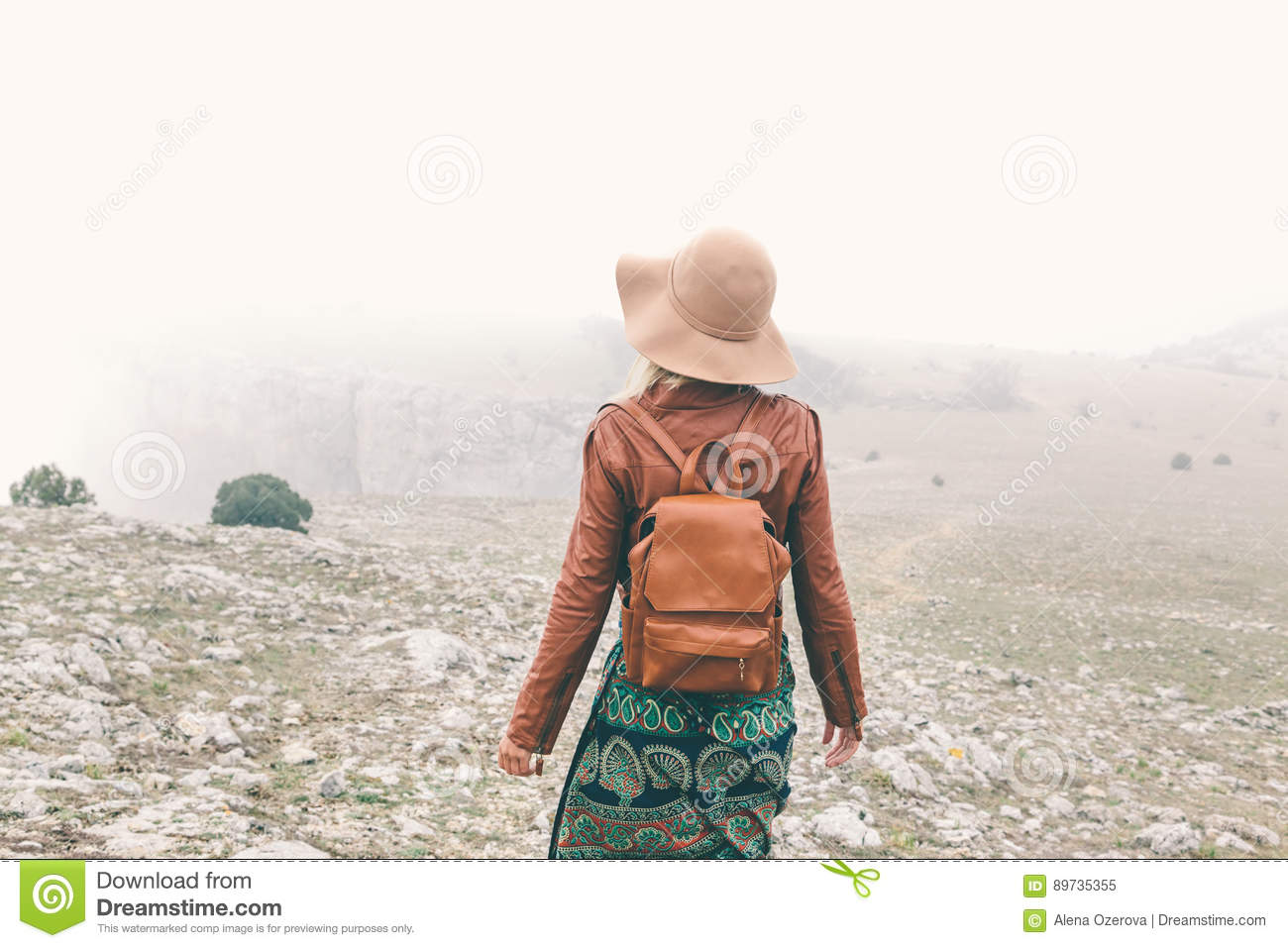 0fde2ce207605 Boho woman wearing hat and leather jacket walking in mountains. Cold  weather and fog. Spring or fall hiking. Wanderlust.