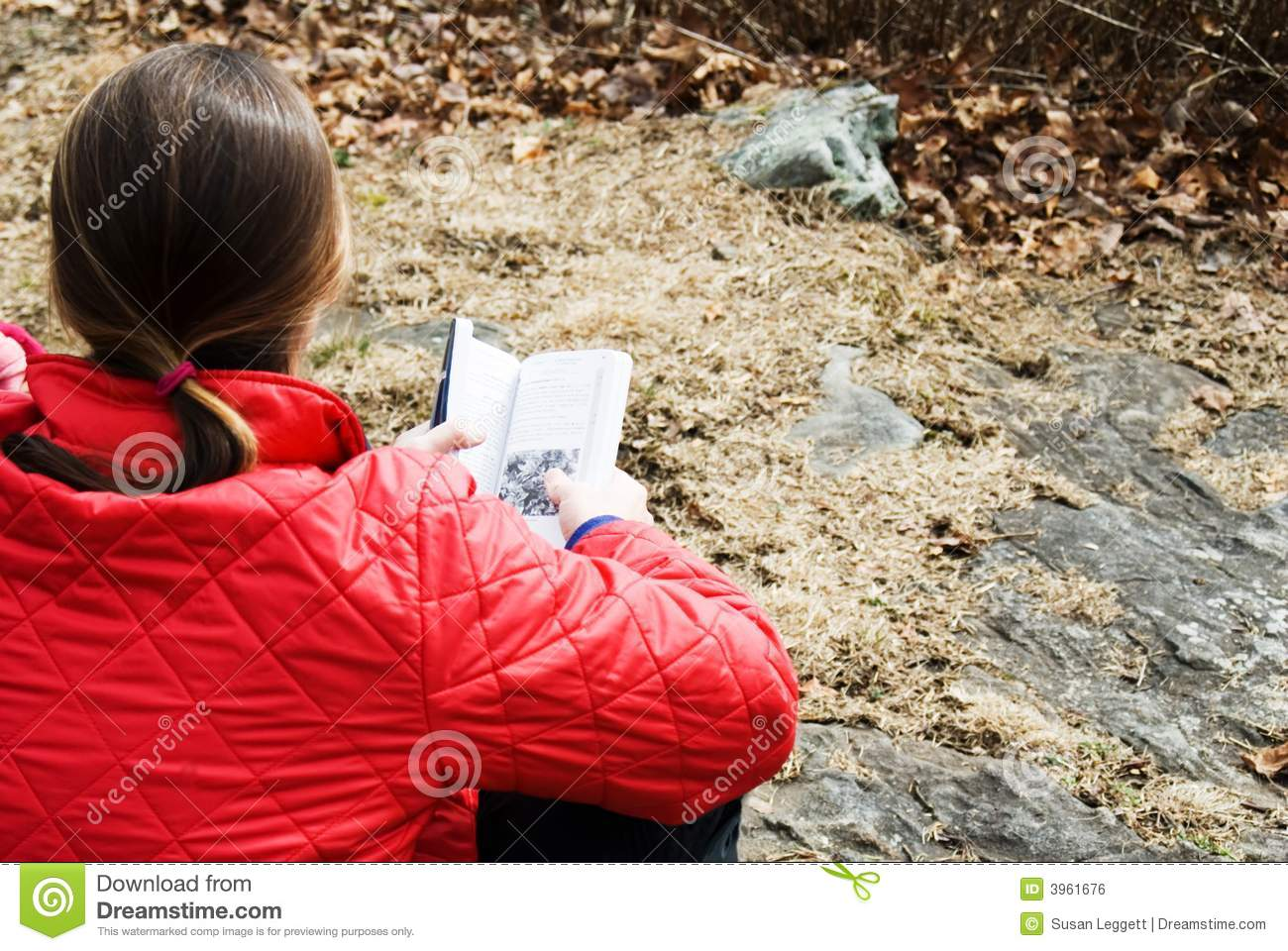 Woman with a book outdoors.