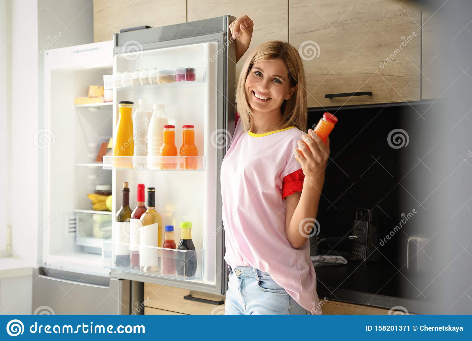 Woman with bottle of juice refrigerator in kitchen