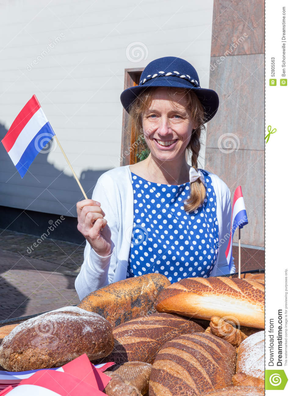 Woman with breads waving with dutch flag