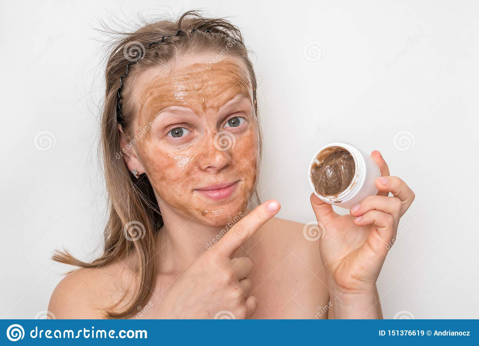 Woman with brown volcanic mask on her face