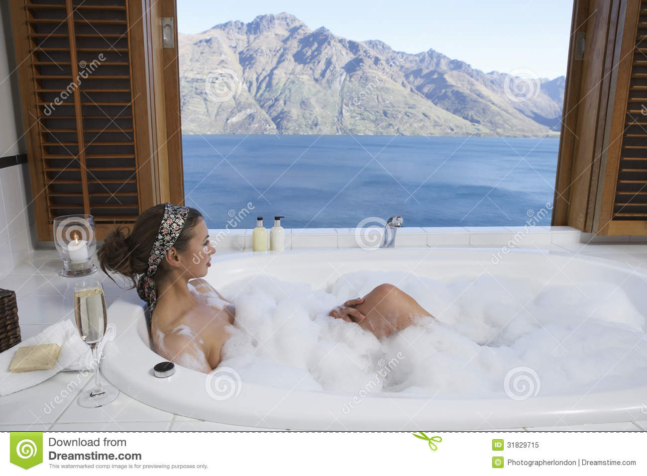 Woman In Bubble Bathtub With Mountain Lake Outside Window Stock ...