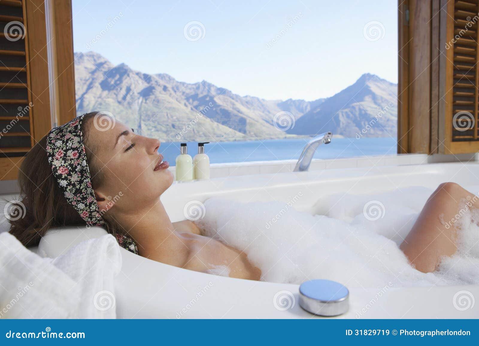 Woman In Bubble Bathtub With Mountain Lake Outside Window Stock ...