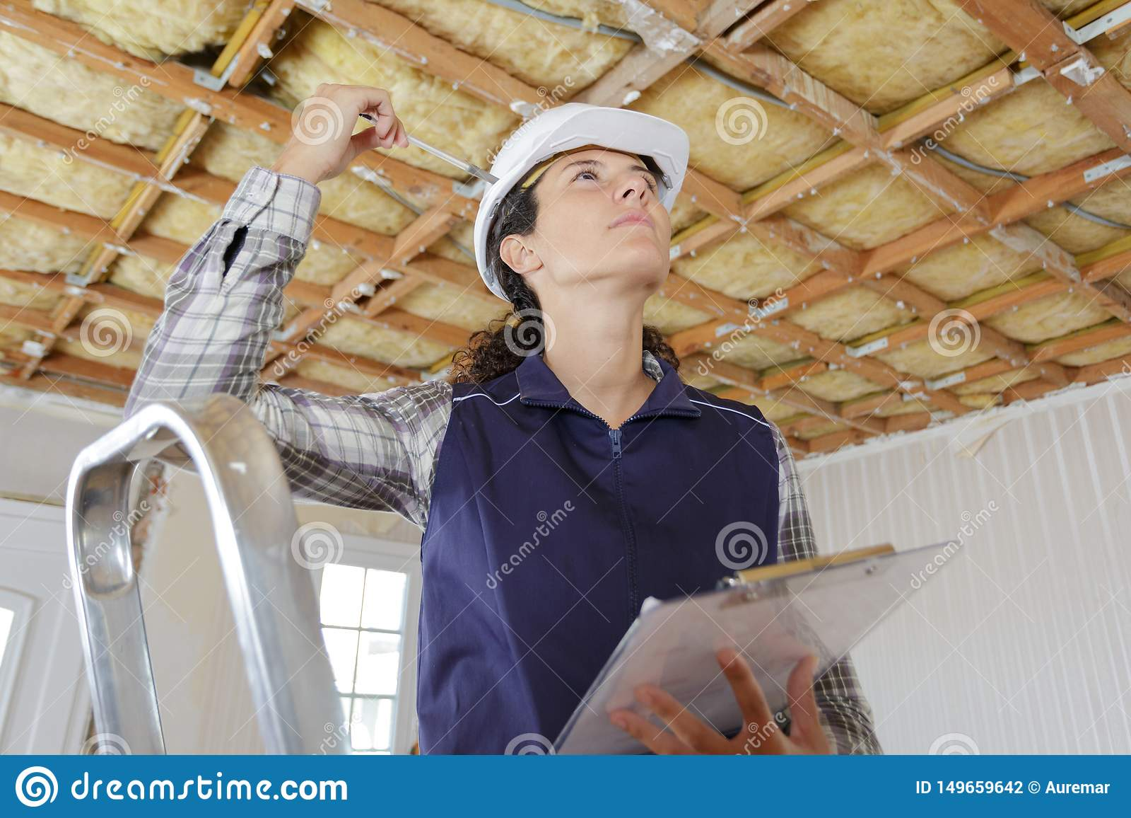 Woman in builder uniform on ladder indoor