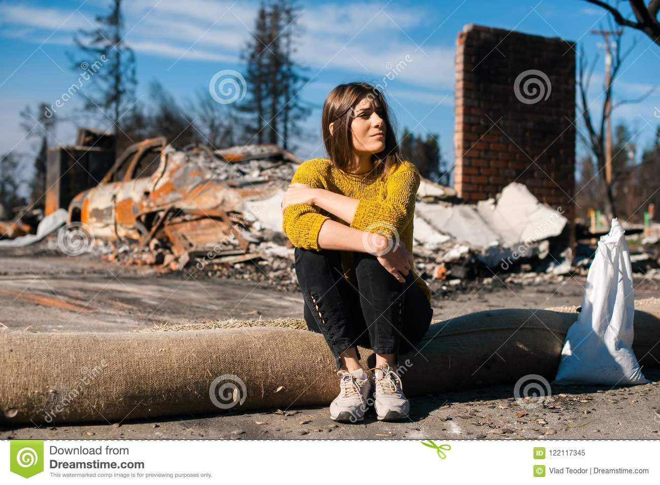 Woman at burned ruined house and yard, after fire disaster