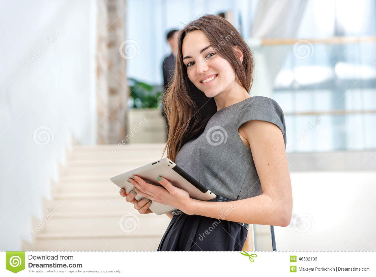 Woman businessman stands on the stairs looking at the camera. Be