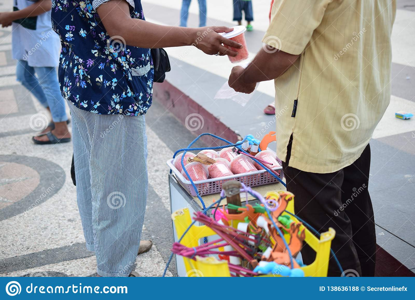 Woman is buying cotton candy to a traditional seller