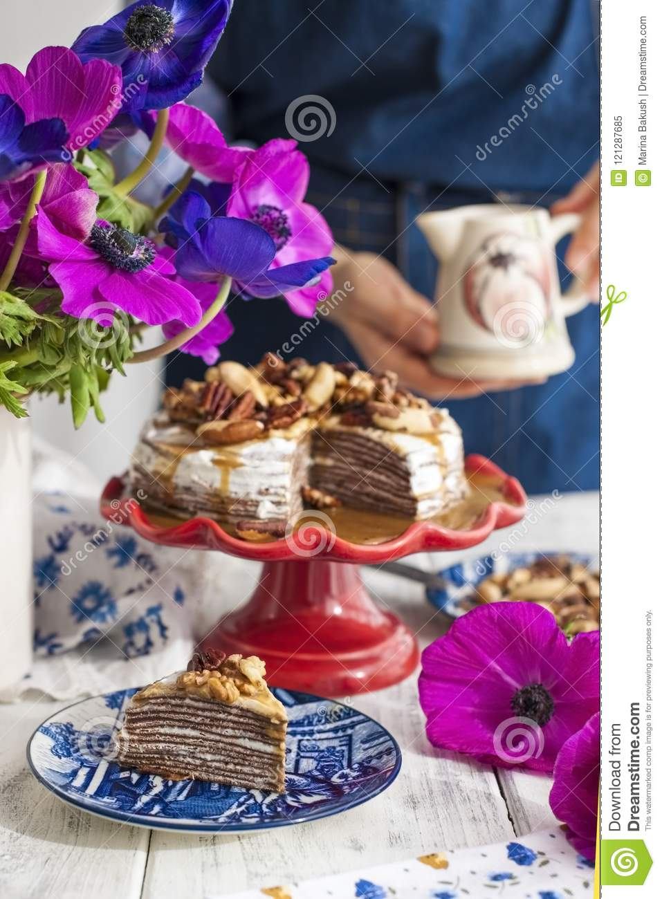 A woman and a cake of thin pancakes with white cream and nuts. Milkman with flowers in the hands of the girl. Spring fresh flowers