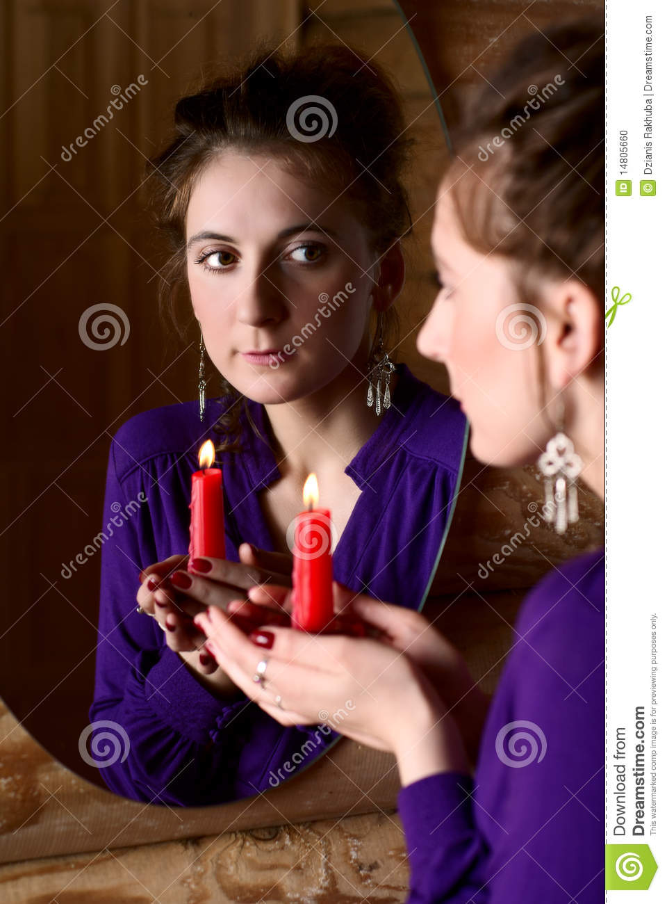 Woman With Candle In Front Of A Mirror Stock Photo