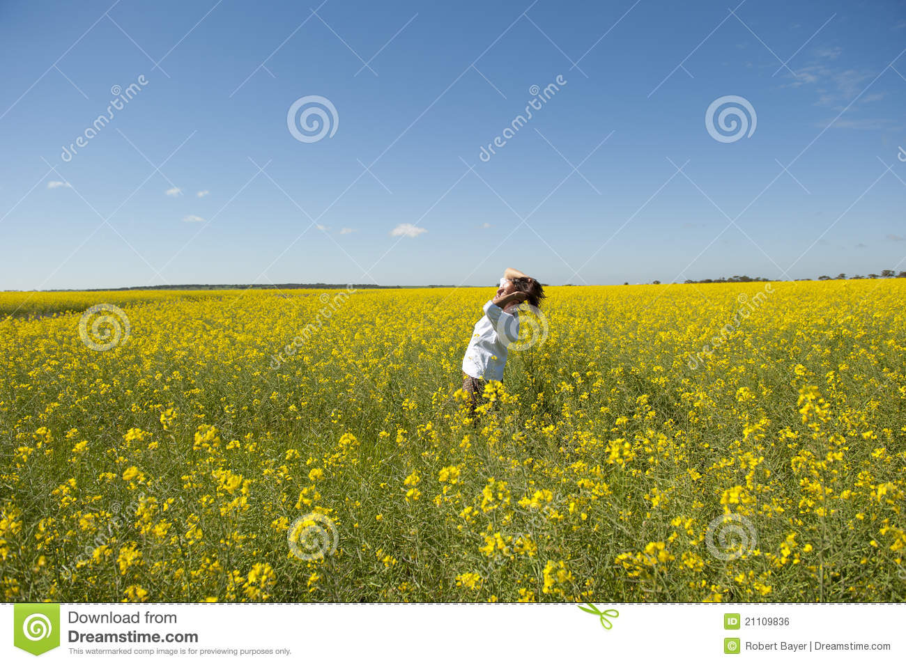 happy mature woman enjoying the sunshine in the middle of a yellow ...
