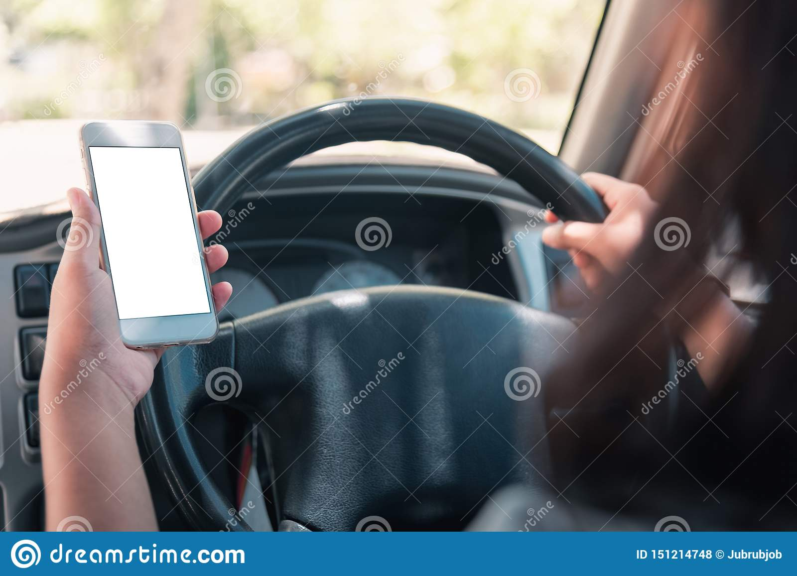 Woman in the car. Young business woman with phone in car. Woman holding smartphone with blank screen