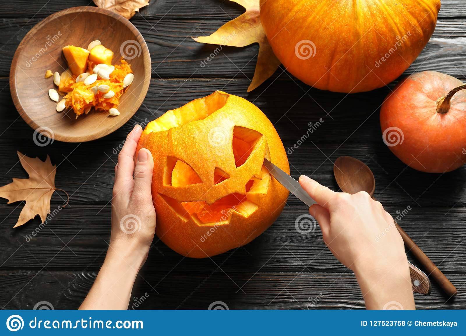 Woman carving Halloween pumpkin head jack lantern on wooden table