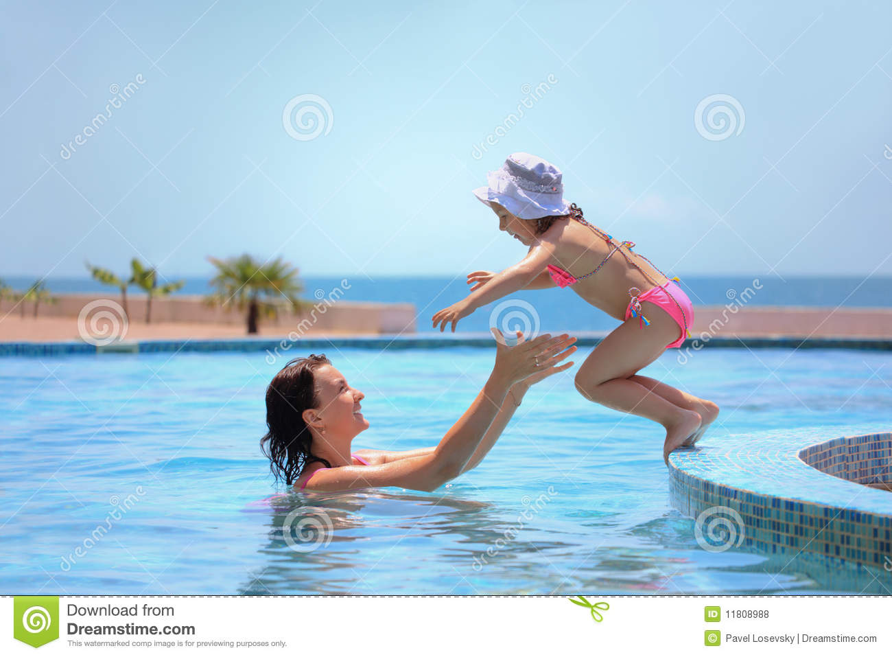 Woman catches girl jumping in pool against sea
