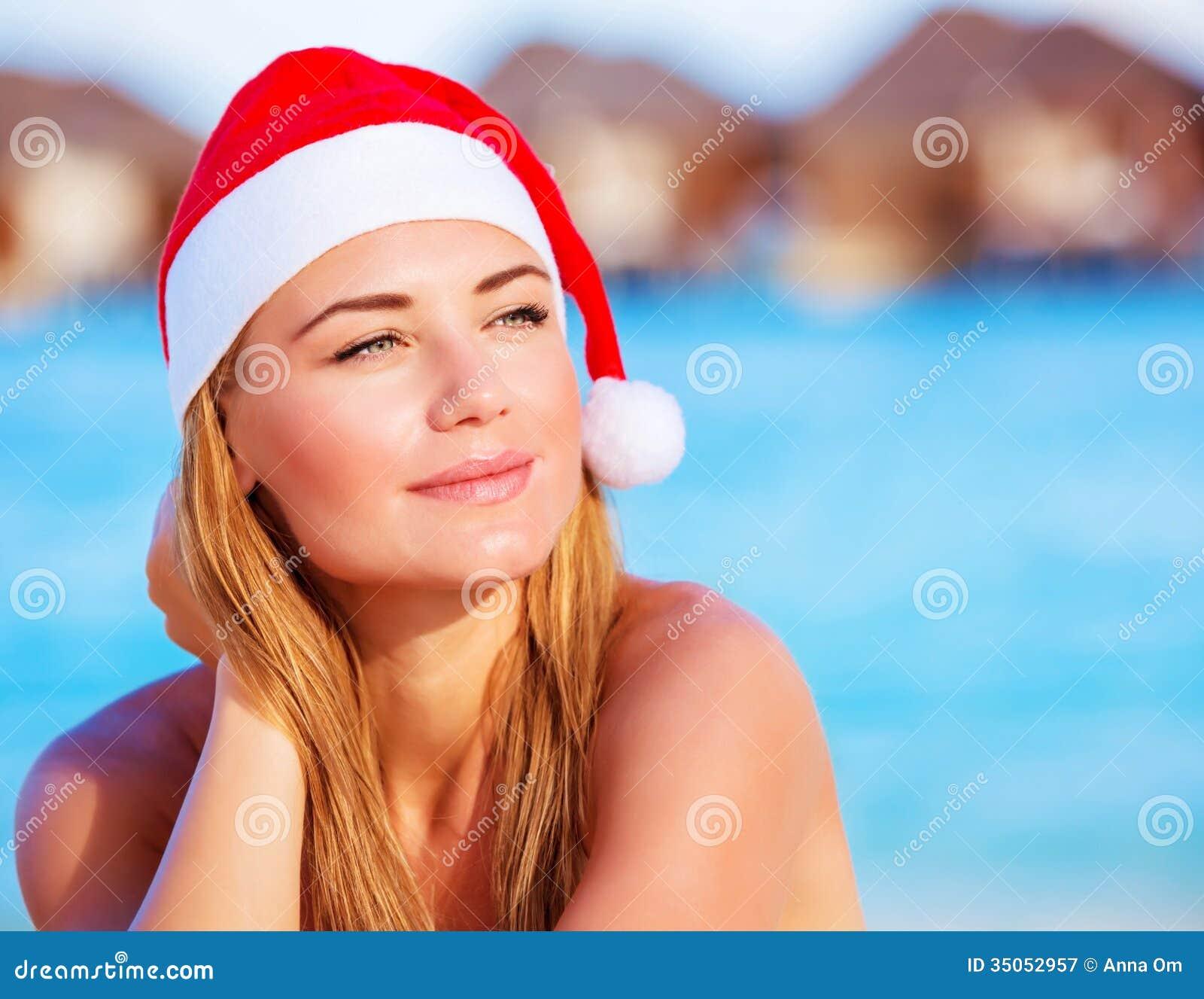 Portrait of cute woman wearing red santa hat celebrating christmas