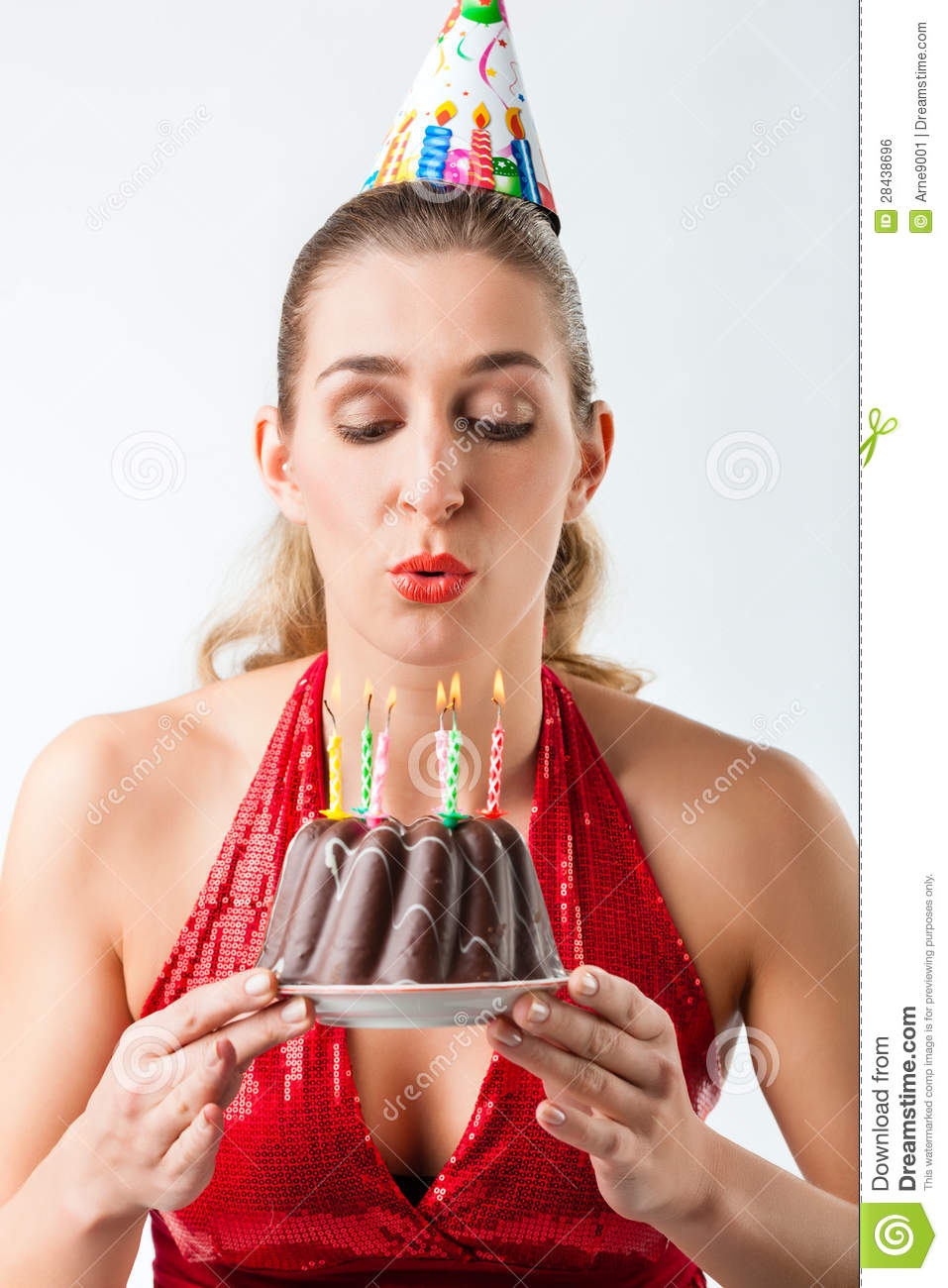 Woman celebrating birthday with cake blowing candles out