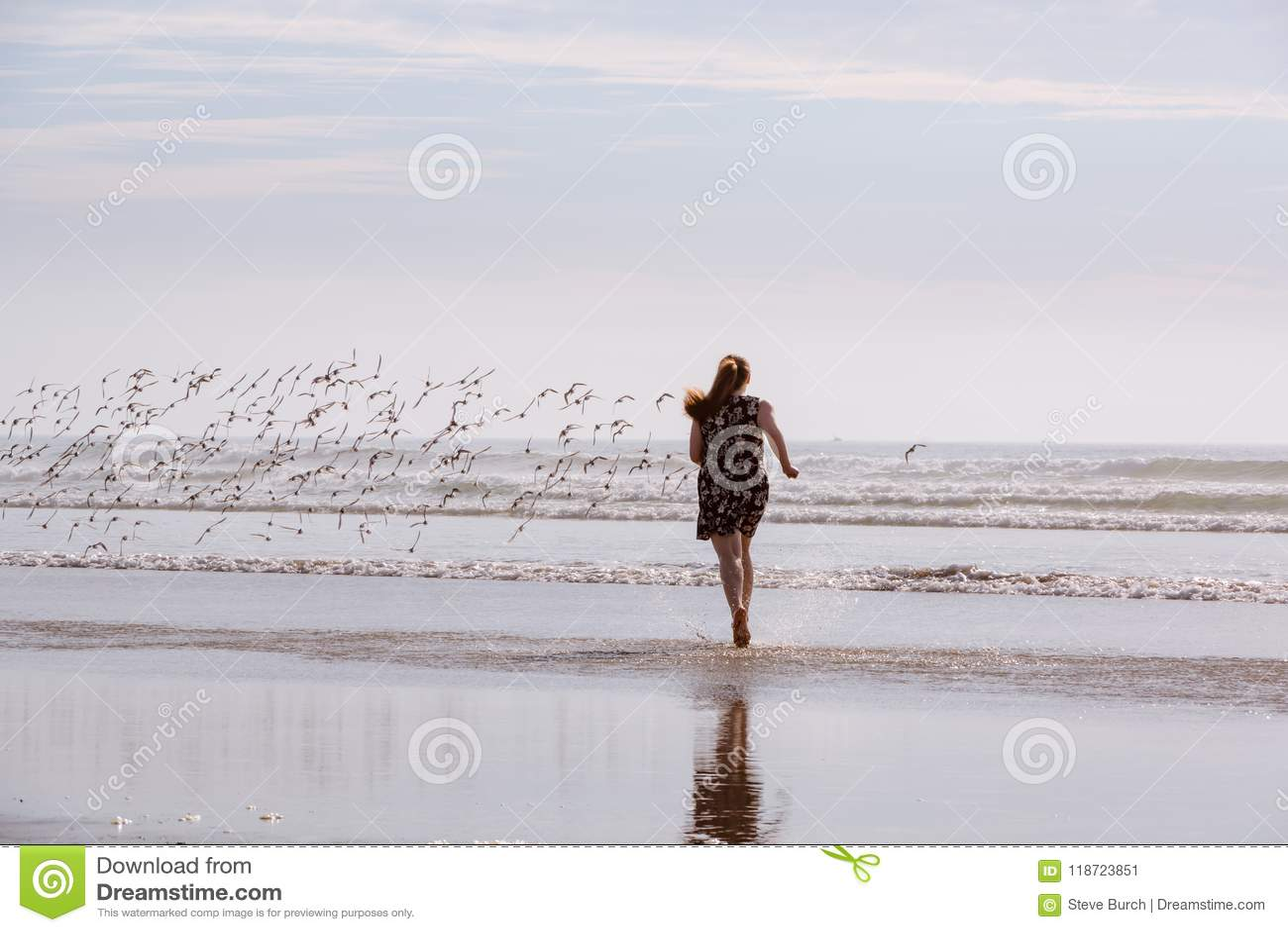 Woman Chasing Birds On Beach