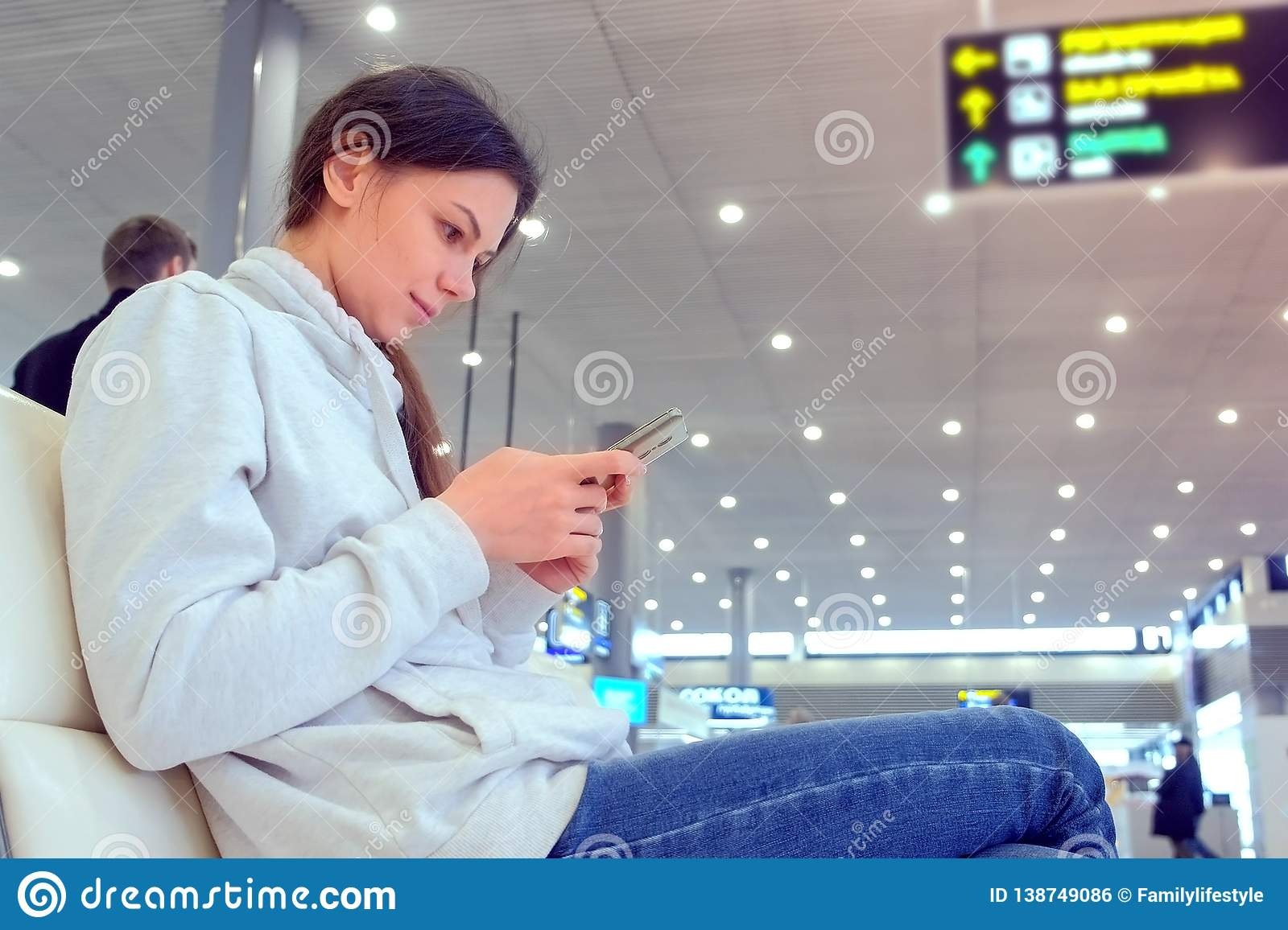 Woman check-in online registration on her mobile phone in airport hall, side view.