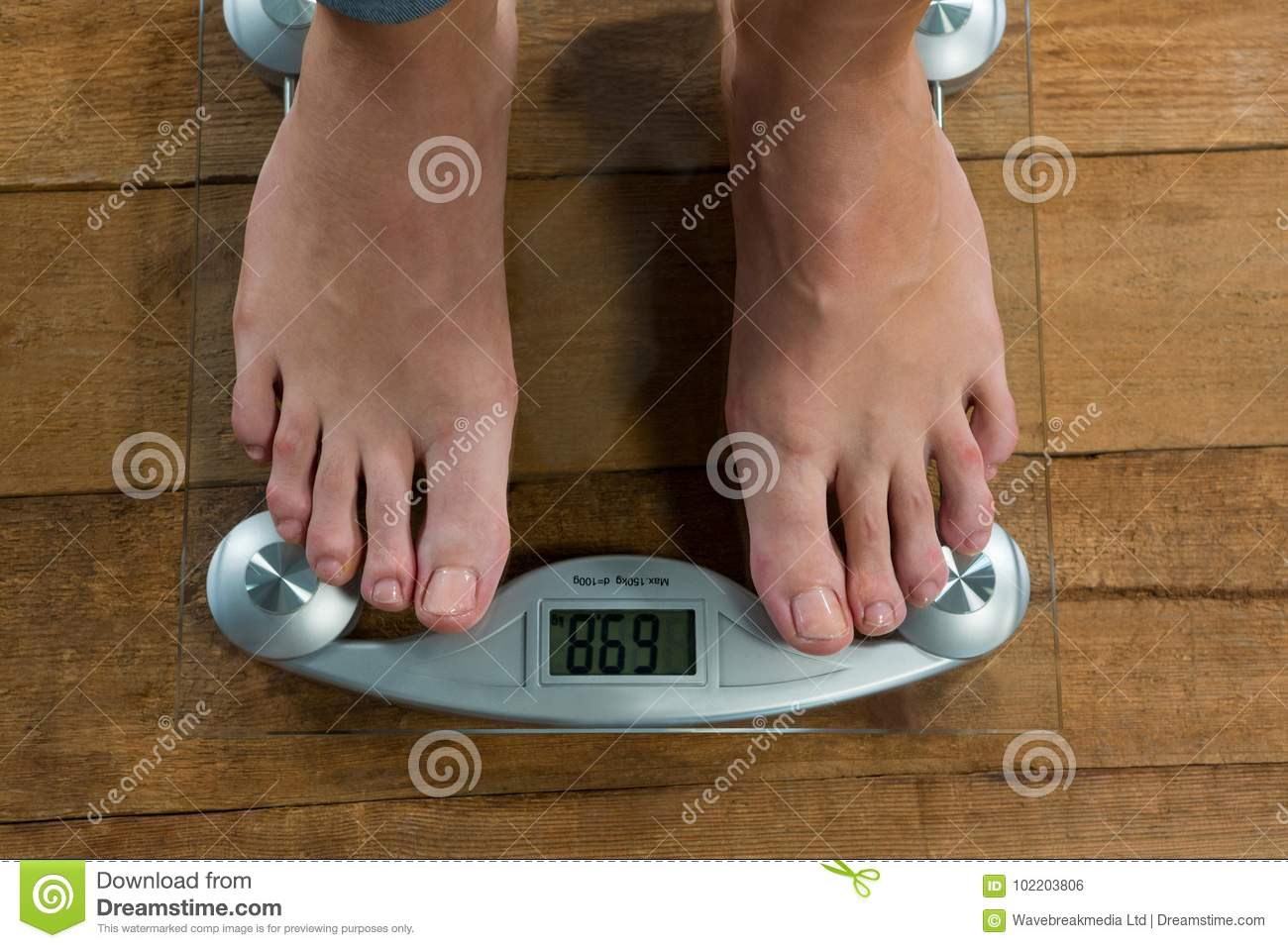 Woman checking her weight on a weighing machine