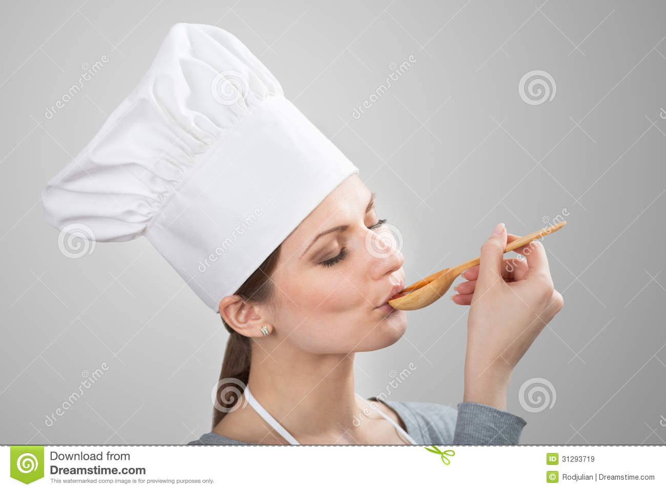 Woman In Chef's Hat Tasting Sauce Stock Image
