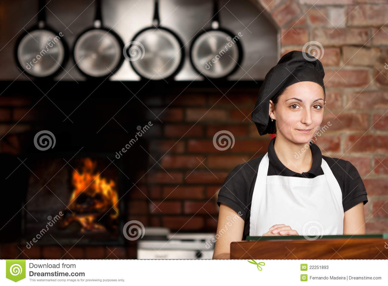 Woman Chef standing in the kitchen with wood oven
