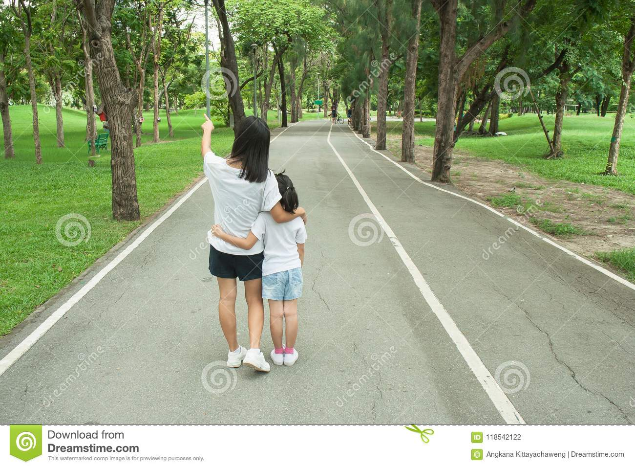 Woman and child walking on footpath and walkway in the public park and feeling happiness and enjoy.