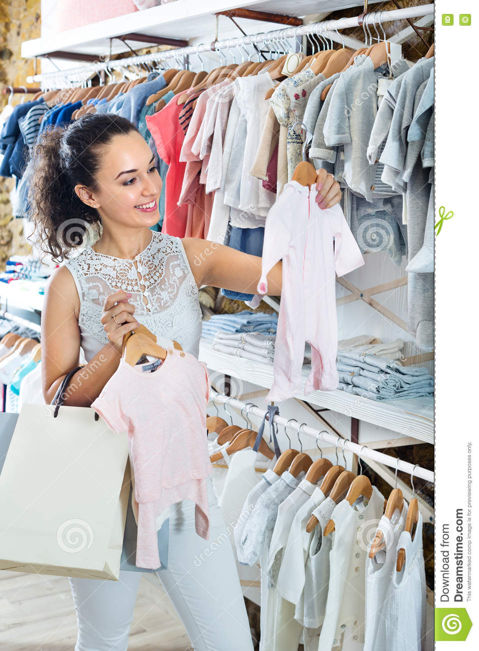 fc397c6718 Young cheerful woman choosing baby pajamas in kids apparel boutique. More  similar stock images