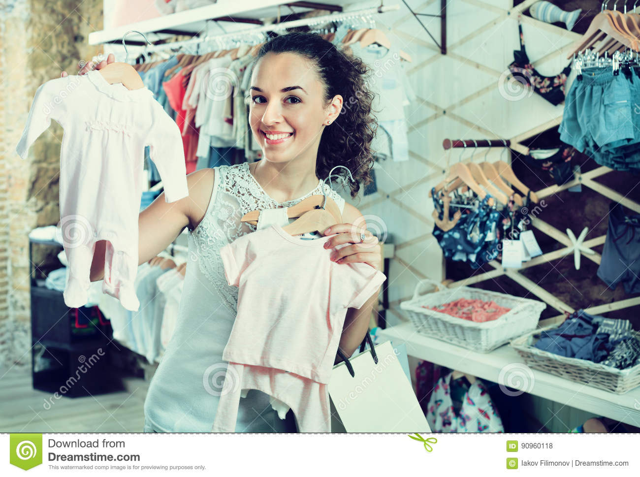 578a290bec Young cheerful woman choosing baby pajamas at a kids apparel boutique. More  similar stock images