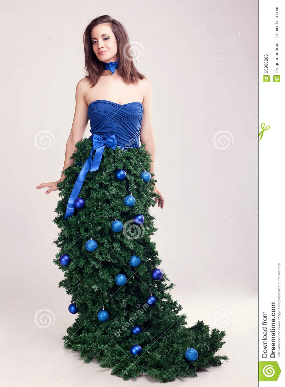 Woman in christmas tree dress on grey background stock How to dress the perfect christmas tree