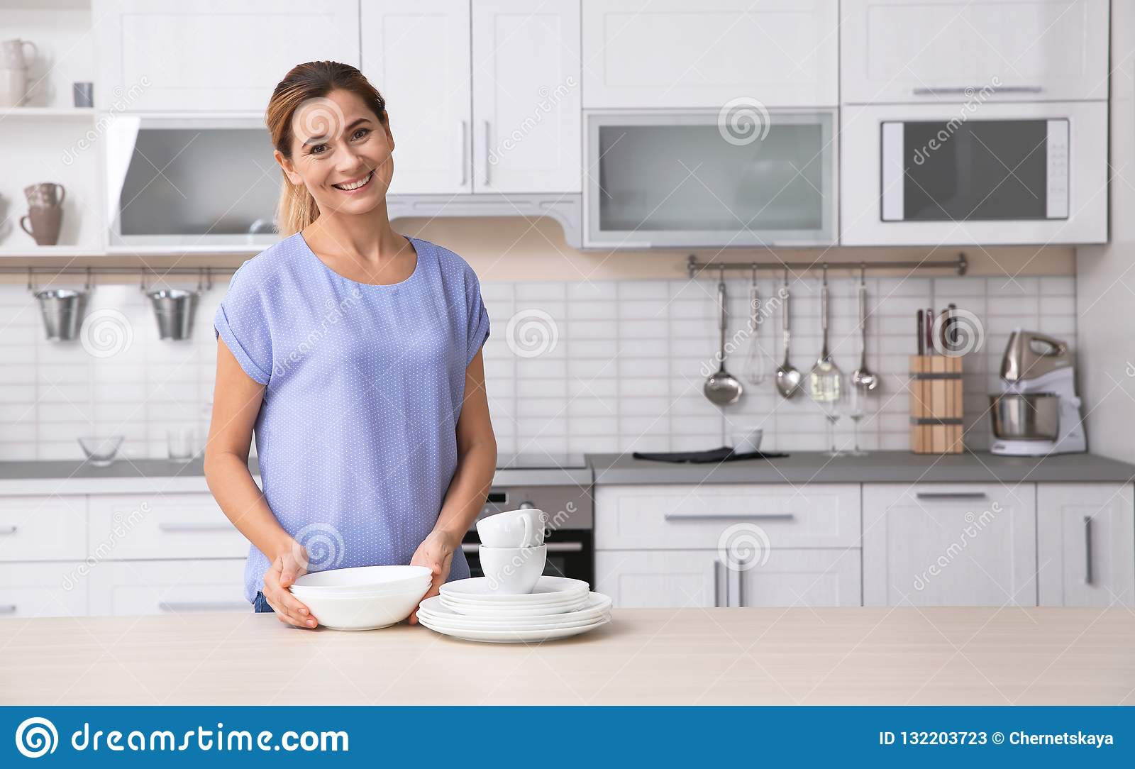 Woman with clean dishes near table in kitchen