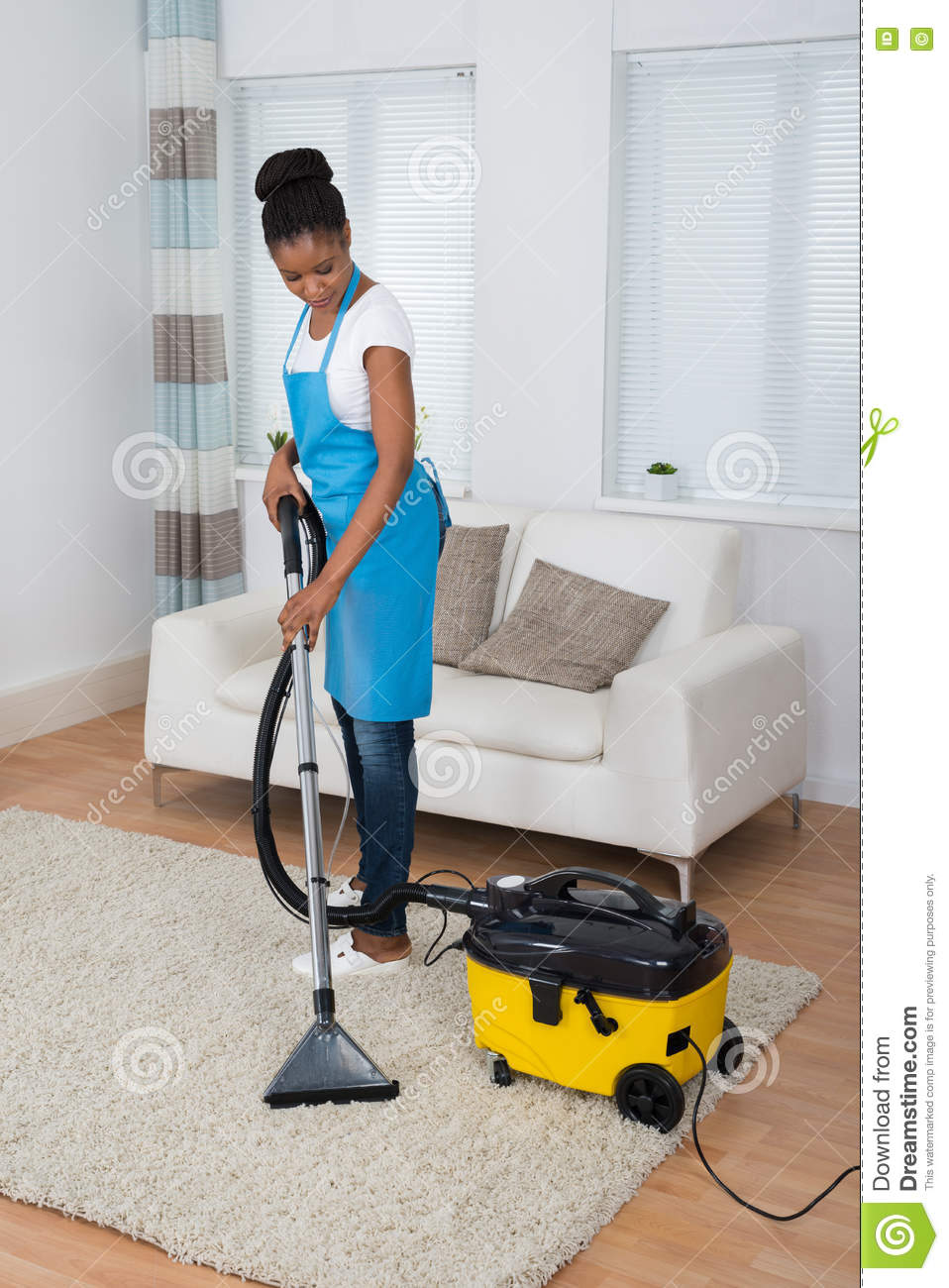 Woman Cleaning Carpet With Vacuum Cleaner Stock Photo
