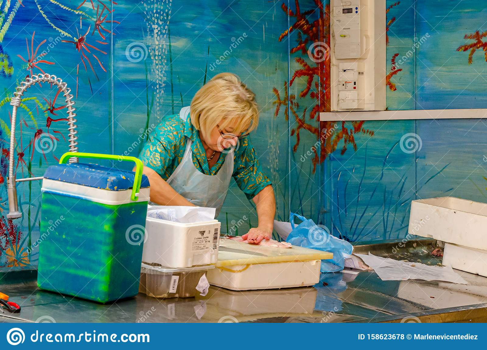 Woman cleaning fish editorial photography. Image of woman