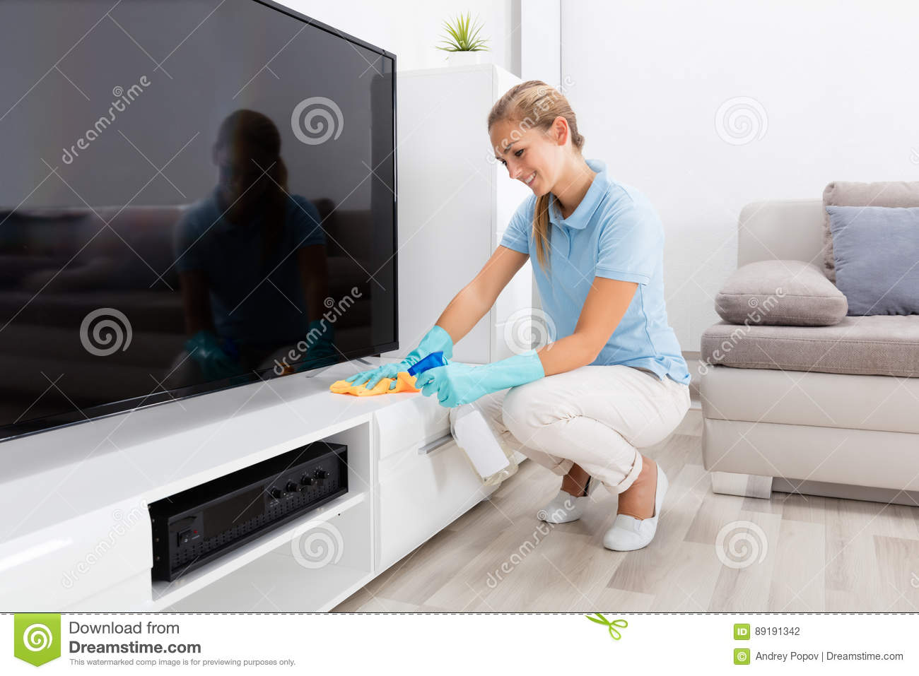 Woman cleaning the furniture of living room stock photo for Cleaning living room furniture