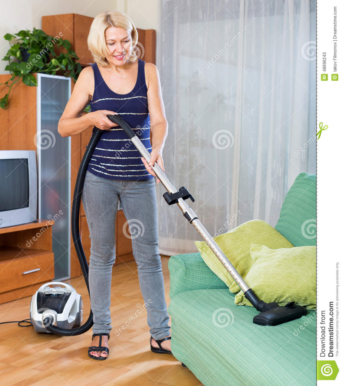 Girl In Jeans Vacuuming The House Royalty Free Stock