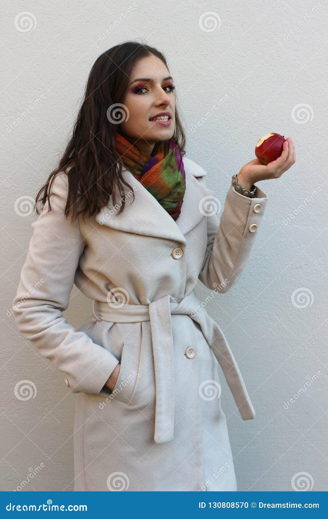 Woman in a coat holding a bitten red juicy apple