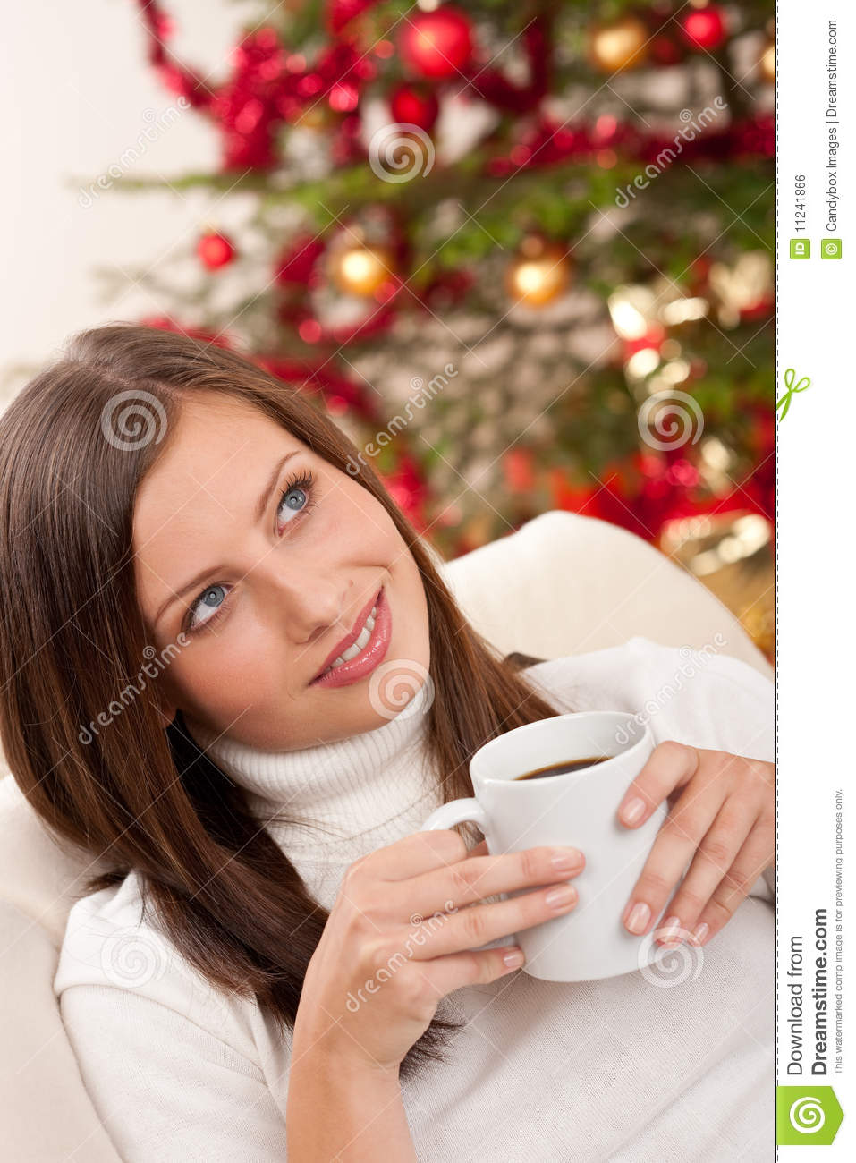 Woman with coffee in front of Christmas tree