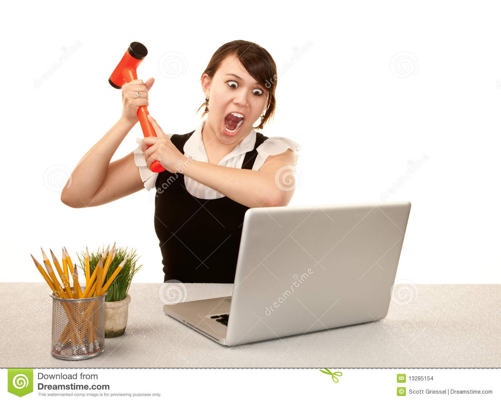 Pretty female office worker destroying laptop computer.
