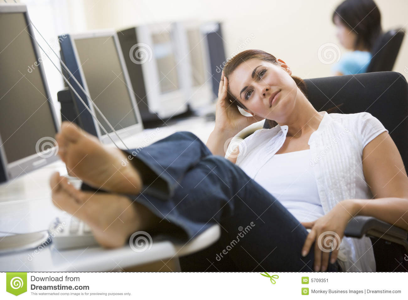 Woman In Computer Room With Feet Up Thinking Stock Image